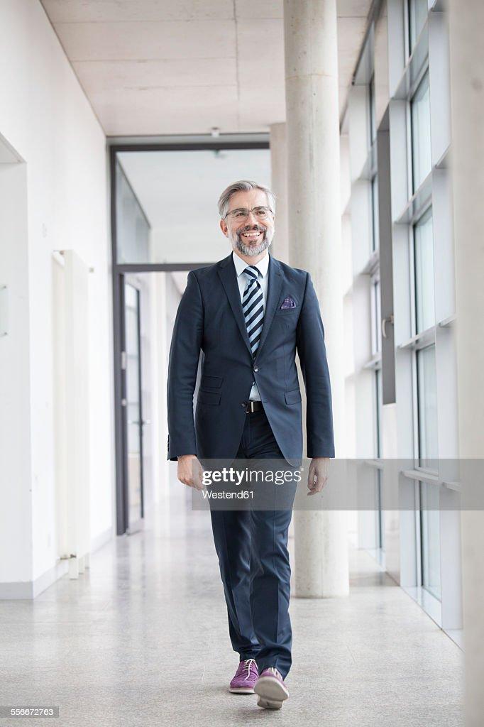 Confident businessman walking on hallway : ストックフォト
