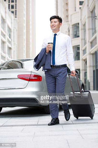 Confident businessman walking with wheeled luggage