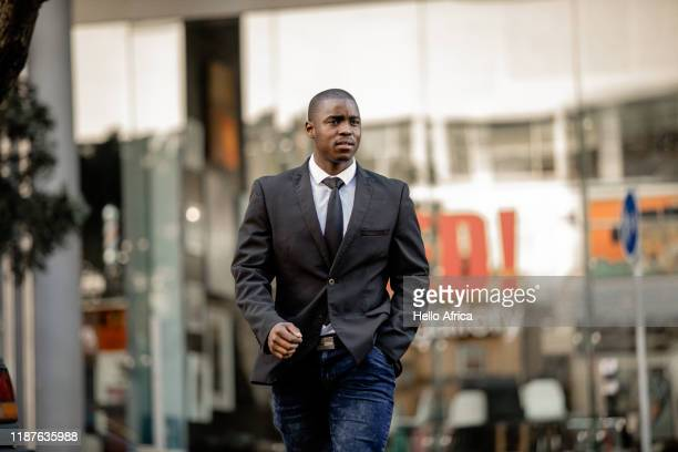 A confident businessman walks through city streets