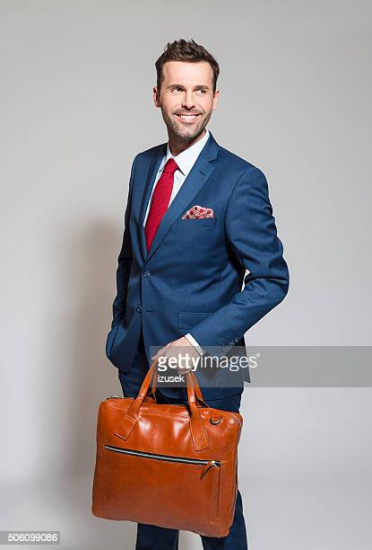 Confident businessman wearing elegant suit, holding briefcase