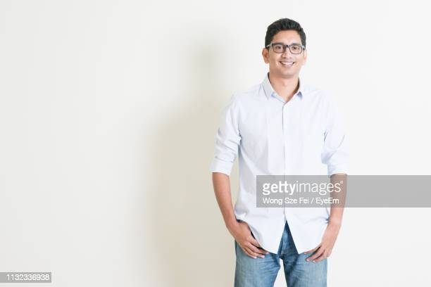 confident businessman wearing smart casual and eyeglasses standing against wall - all shirts ストックフォトと画像