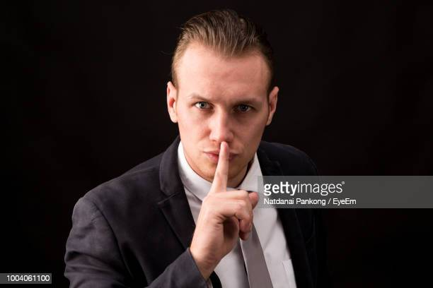 confident businessman wearing suit against black background - finger on lips stock pictures, royalty-free photos & images