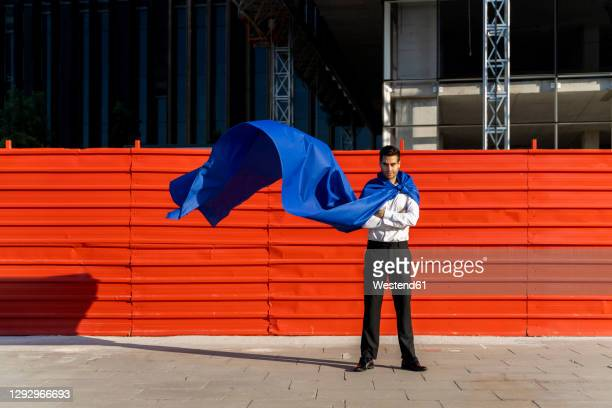 confident businessman wearing superhero cape in the city - cape stock pictures, royalty-free photos & images