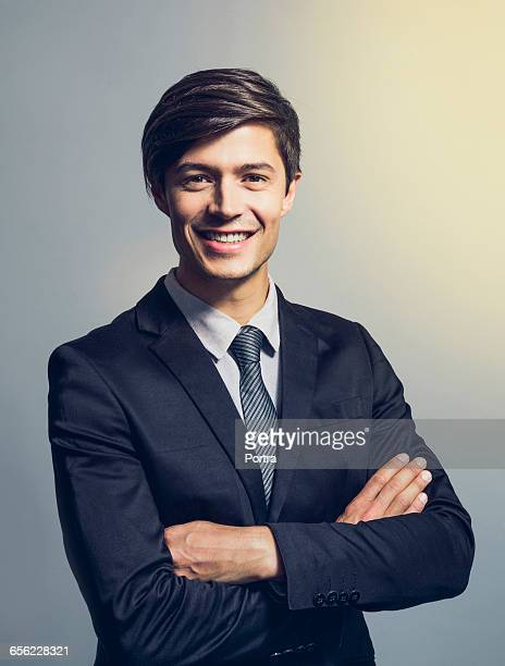 confident businessman with arms crosse - スーツ ストックフォトと画像
