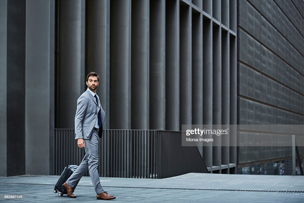 Confident businessman with bag against building : Stock-Foto