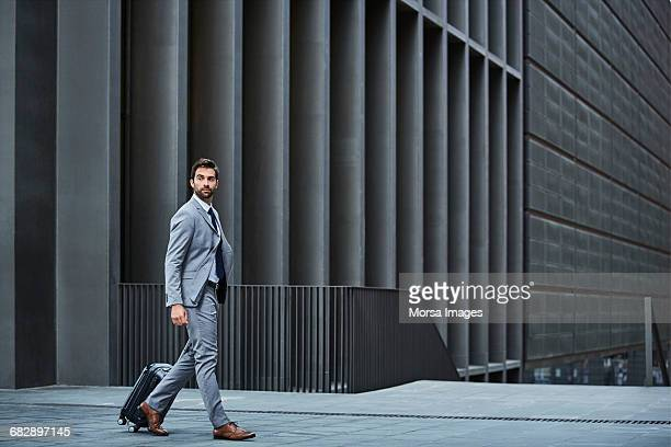 confident businessman with bag against building - elegancia fotografías e imágenes de stock