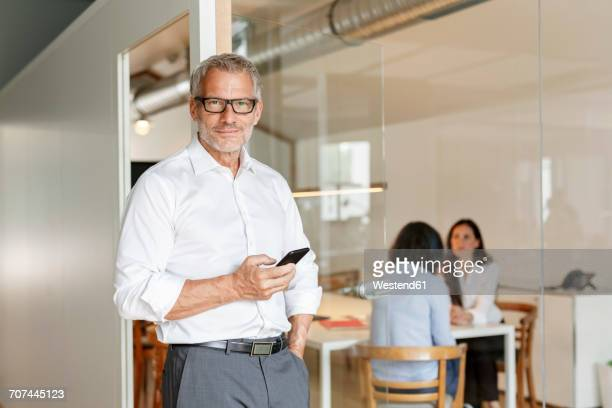 Confident businessman with cell phone in office with employees in background
