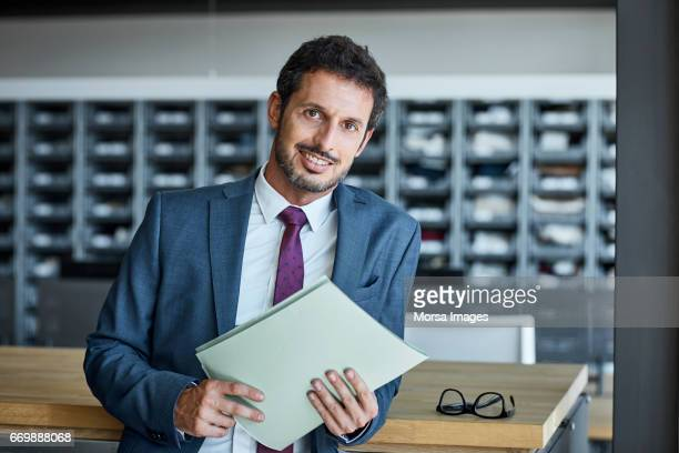 Confident businessman with file in textile factory