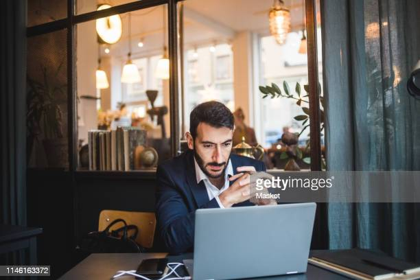 confident businessman with hands clasped looking at laptop on desk in creative office - incidental people stock pictures, royalty-free photos & images