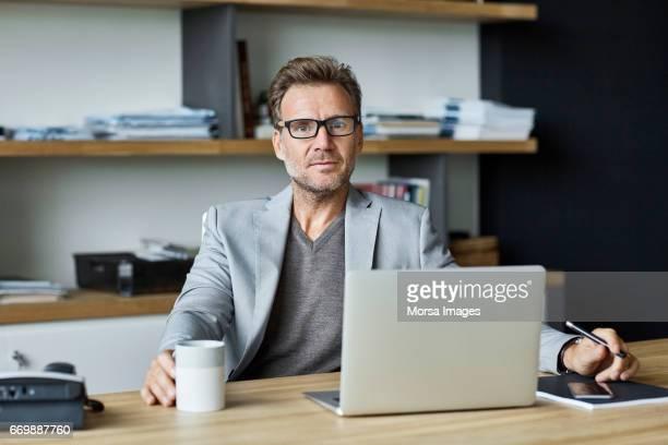 Confident businessman with laptop at desk