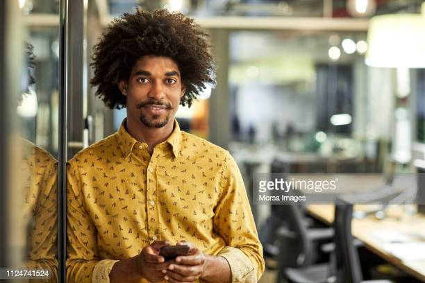 confident businessman with mobile phone in office - us kultur stock-fotos und bilder