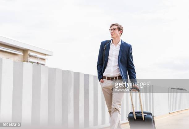 confident businessman with rolling suitcase walking at parking garage - ジャケット ストックフォトと画像