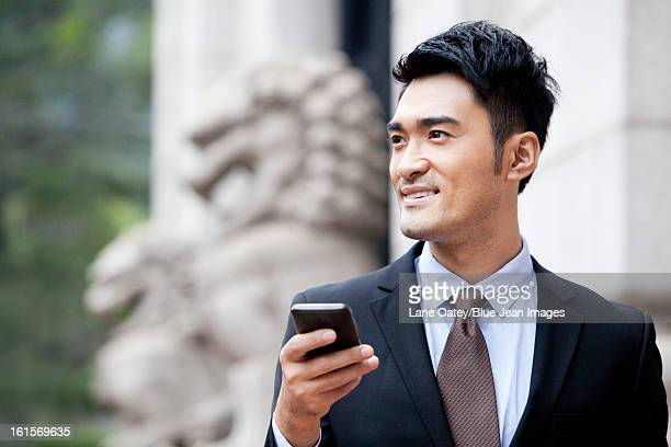 Confident businessman with smart phone looking at view, Hong Kong