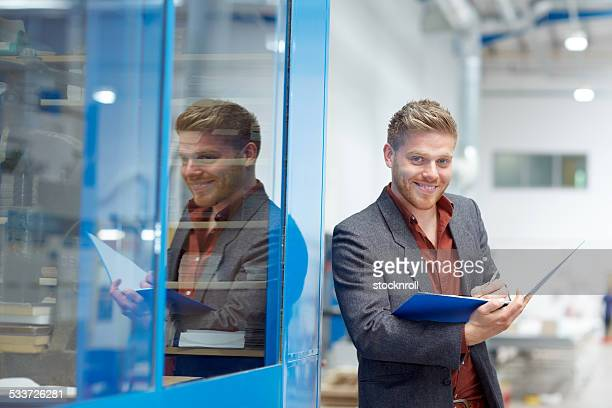 Confident businessman working at factory