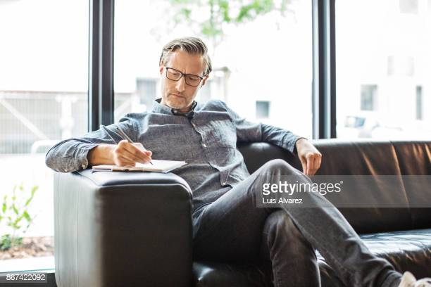 confident businessman writing on clipboard in creative office - smart casual stock pictures, royalty-free photos & images