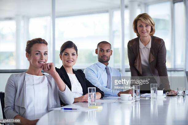 Confident businesspeople at conference table