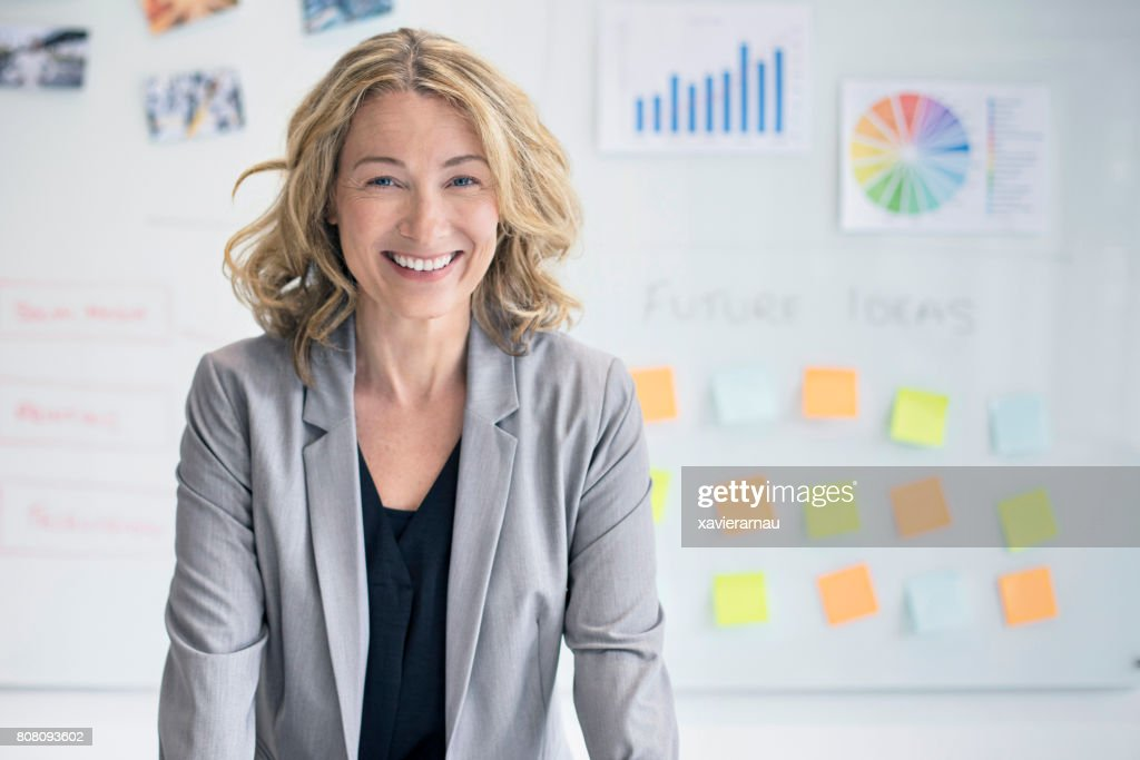 Confident businesswoman against whiteboard : Stock Photo