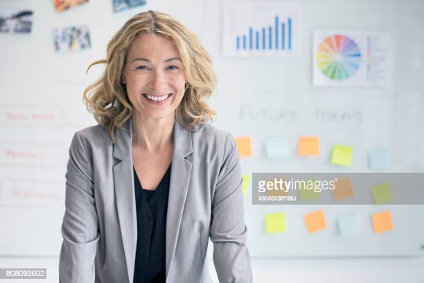 femme d'affaires confiant contre whiteboard - affaires finance et industrie photos et images de collection