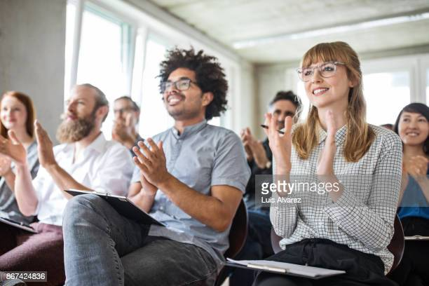 Confident businesswoman and colleagues applauding during meeting