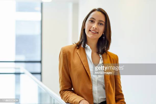 confident businesswoman at coworking space - brown jacket stock pictures, royalty-free photos & images