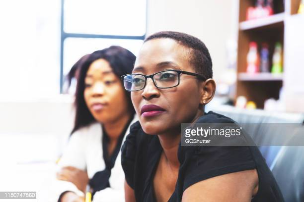 confident businesswoman attending a staff meeting - chairperson stock pictures, royalty-free photos & images