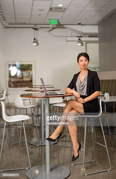 confident businesswoman crossing legs on high chair - most beautiful legs stock photos and pictures