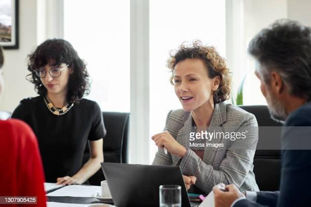 confident businesswoman discussing strategy with colleagues in board room - adulto de idade mediana imagens e fotografias de stock