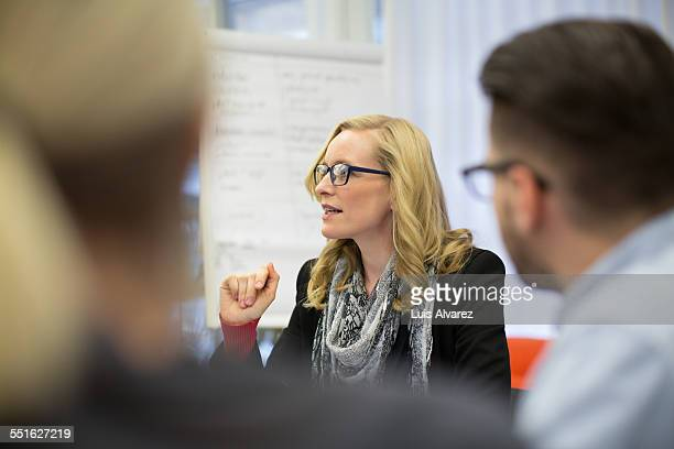 Confident businesswoman discussing with colleagues