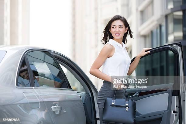 Confident businesswoman getting off car