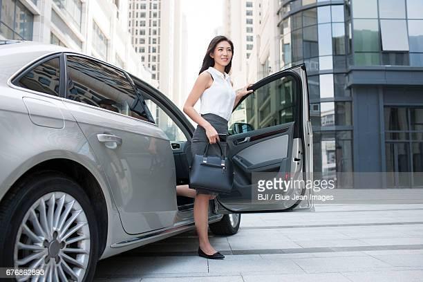 confident businesswoman getting off car - 降り立つ ストックフォトと画像