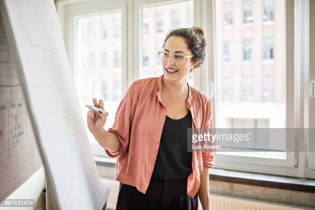 confident businesswoman giving presentation in creative office - smart casual stock pictures, royalty-free photos & images
