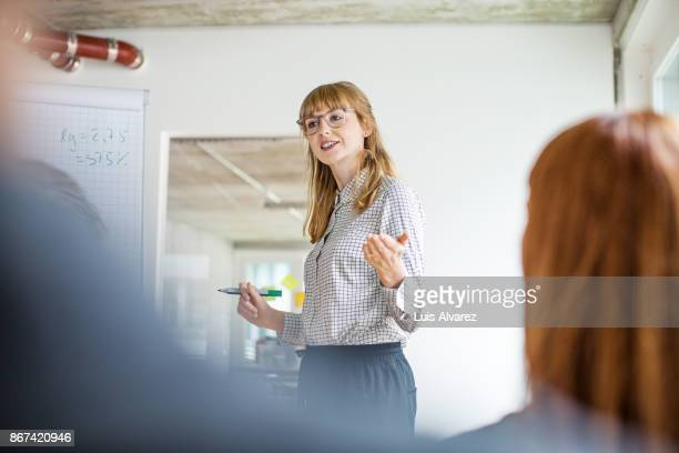 confident businesswoman giving presentation to colleagues in office - vortrag stock-fotos und bilder