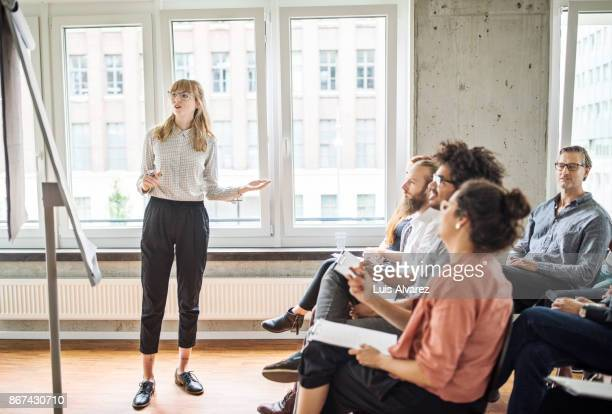 confident businesswoman giving presentation to coworkers - tonen stockfoto's en -beelden