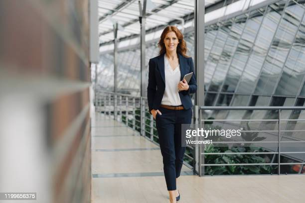 confident businesswoman holding a tablet in a modern office building - direttrice foto e immagini stock