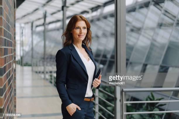 confident businesswoman holding a tablet in a modern office building - manager stock pictures, royalty-free photos & images