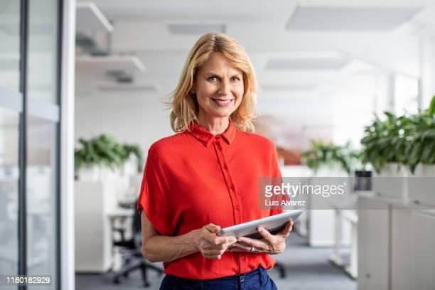 confident businesswoman holding digital tablet in office - une seule femme d'âge mûr photos et images de collection