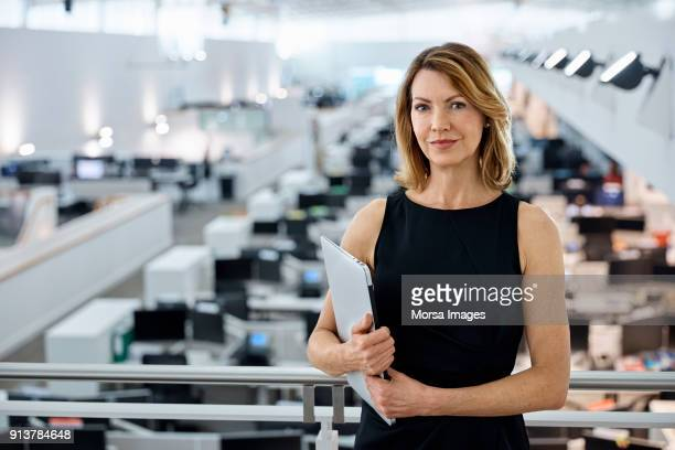 Confident businesswoman holding laptop in office