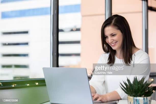 zelfverzekerde onderneemster is financieel adviseur die met technologie in bureau werkt - werkneemster stockfoto's en -beelden