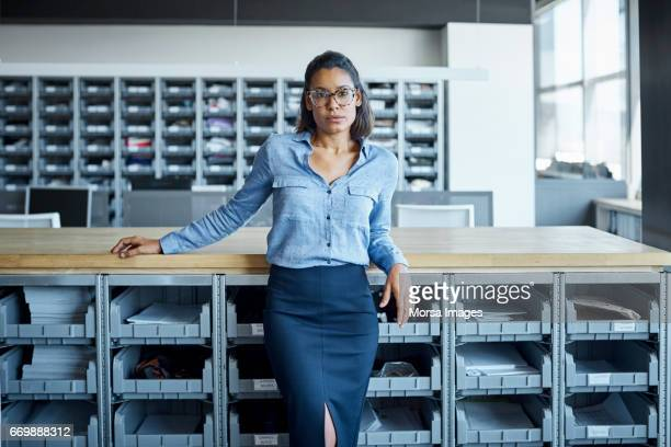 confident businesswoman leaning in textile factory - skirt stock pictures, royalty-free photos & images