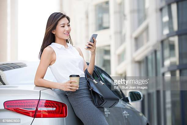 Confident businesswoman leaning on car with smart phone