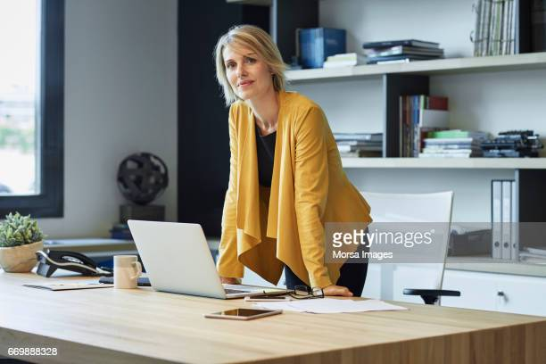 confident businesswoman leaning on desk - yellow stock pictures, royalty-free photos & images