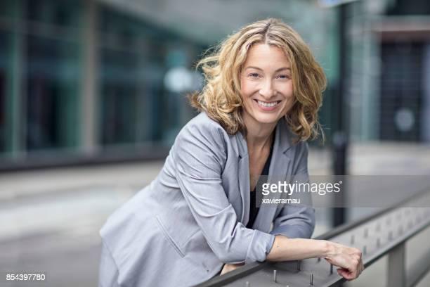 Zuversichtlich, Geschäftsfrau, stützte sich auf Geländer