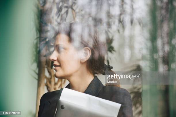 confident businesswoman looking away seen through window at office - photographed through window stock pictures, royalty-free photos & images