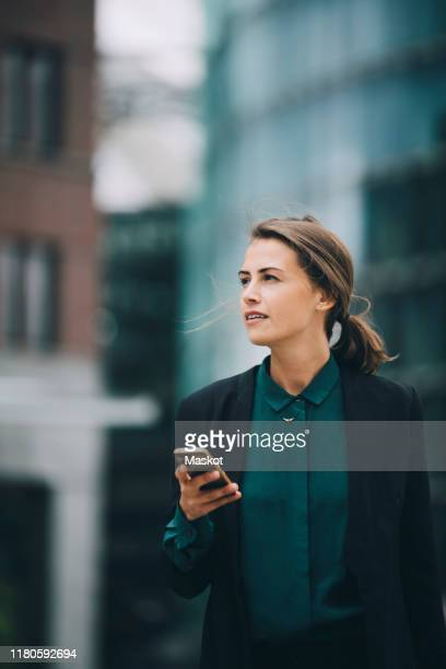 confident businesswoman looking away while holding smart phone in city - europa occidentale foto e immagini stock
