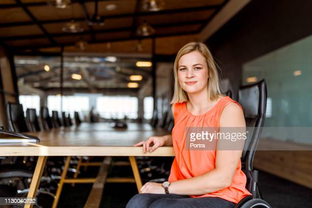 confident businesswoman on wheelchair in board room - disabilitycollection stock pictures, royalty-free photos & images