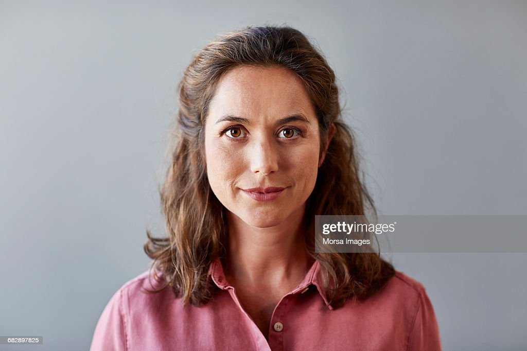 Confident businesswoman over gray background : Stock Photo