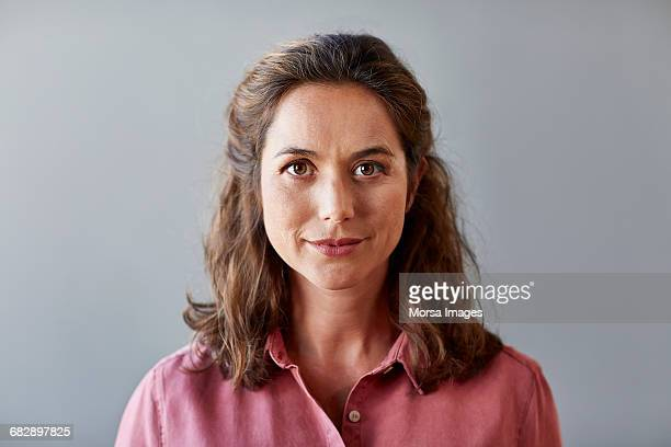confident businesswoman over gray background - portret stockfoto's en -beelden