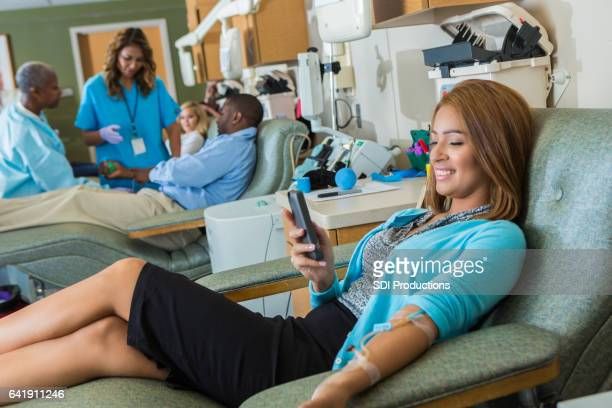 confident businesswoman passes the time while donating blood - blood donation stock photos and pictures