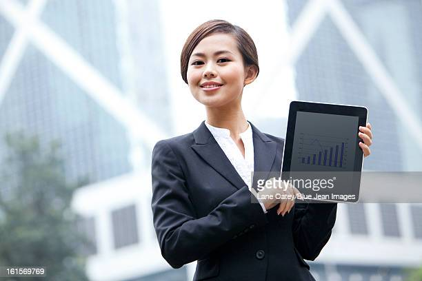 Confident businesswoman showing digital tablet, Hong Kong