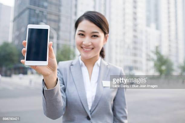 Confident businesswoman showing smart phone